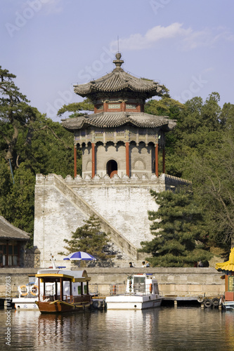 Chinese style tower in a park, surrounded by willow trees