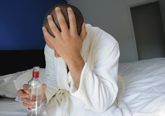 Young man sitting on the edge of bed, drinking alcohol