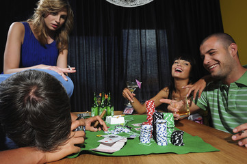 Group of young adults playing poker
