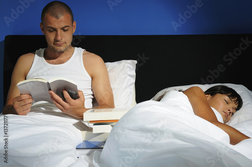 Young man reading while young woman sleeps in bed, studio shot