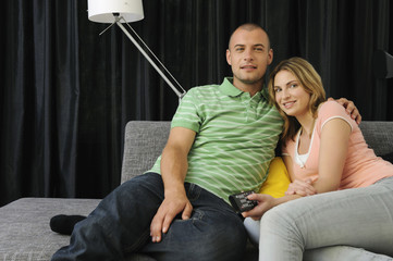 Portrait of young couple sitting on couch, holding remote control