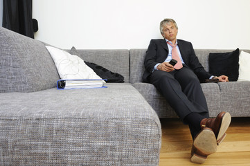 Portrait of businessman relaxing on couch holding remote control