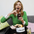 Portrait of woman sitting on couch eating sweets
