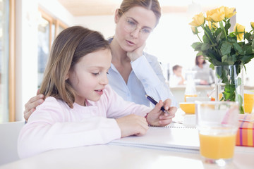 Portrait of mother helping daughter with homework