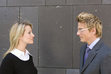 Portrait of businessman and businesswoman standing outside office building