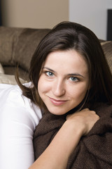 Portrait of young woman lying on couch indoors