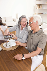 Happy senior couple at breakfast table pouring coffee