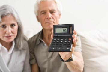 Senior couple holding calculator