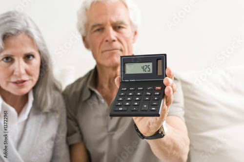Senior couple holding calculator