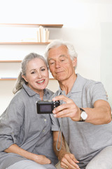 Senior couple taking photo of each other with digital camera