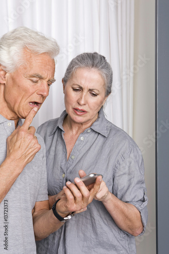 Senior couple looking at cell phone