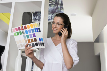 Young businesswoman on the phone looking at color swatches