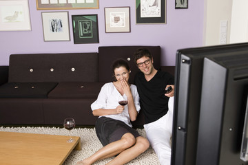 Young couple watching TV together