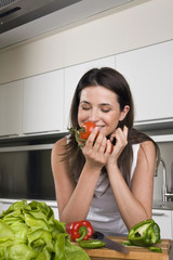 Young woman smelling tomatoes in kitchen