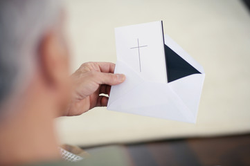 Close-up of senior man holding card with cross