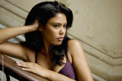 Young mixed race woman leaning on banister, close-up