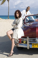 Young multi-ethnic couple with car on beach, young woman leaning on car in foreground, Havana, Cuba