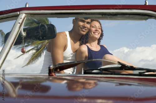 Young multi-ethnic couple sitting in car, low angle view, Havana, Cuba