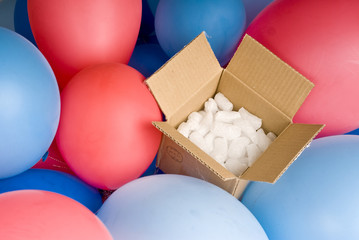open gift box surrounded by colorful balloons