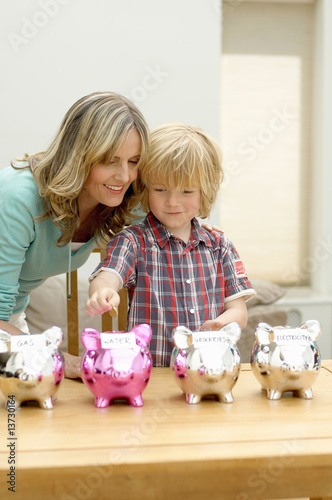 Mother and son putting coin in piggy bank, smiling, Den Haag, Netherlands
