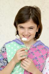 bambina sorridente con fiore - margherita