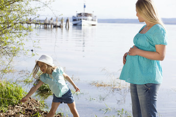 Pregnant woman and daughter on waterfront