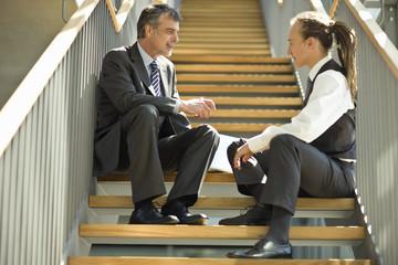 Businessmen sitting on staircase talking