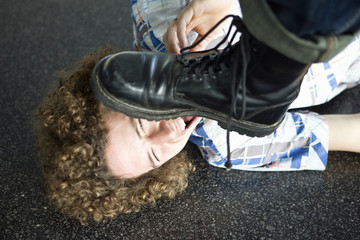 Young man lying on ground about to be stepped on