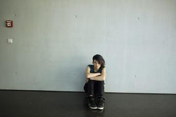 Sullen teenage girl sitting on floor in barren room