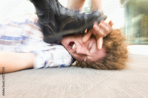 Young man lying on ground being stepped on by someone wearing black boot