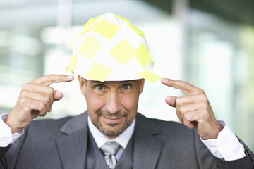 Portrait of mature man pointing at hardhat with note papers stuck to it