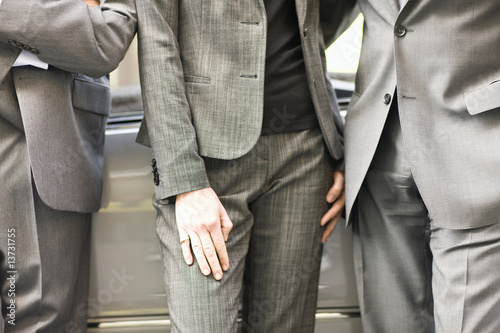 Midsection view of three colleagues in business suits