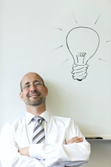 Portrait of mature man sitting beneath a line drawing of light bulb