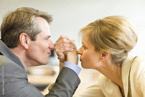 Mature man and woman enjoying a friendly bout of arm wrestling