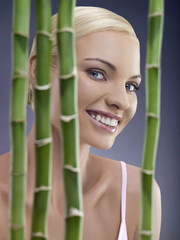 Portrait of young woman behind bamboo, studio shot