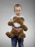 Young boy hugging a teddy bear wearing a mask, studio shot