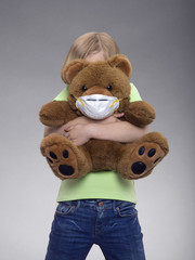 Young girl hugging a teddy bear wearing a mask, studio shot