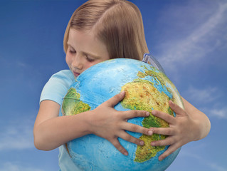 Young girl hugging a globe, studio shot