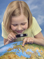 Young girl looking through a magnifying glass at a globe, studio shot