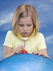 Young girl listening to globe through a toy stethoscope, studio shot