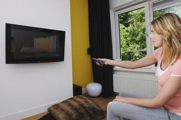 Portrait of young woman turning on television