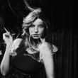 Portrait of woman smoking, black and white studio shot