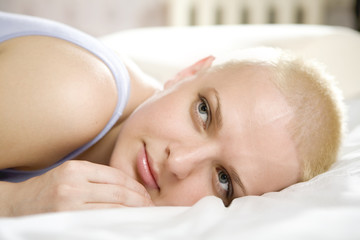 portrait of young blond bald woman lying on the sofa