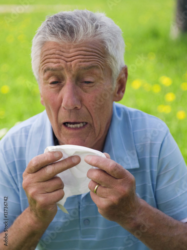 Senior man sneezing outdoors