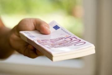 Hand mit Geldbündel