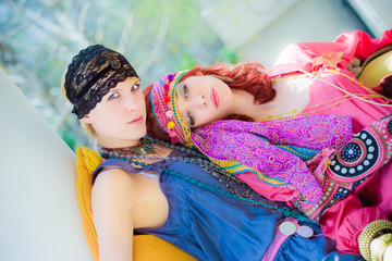 couple of women in colorful clothes resting in garden