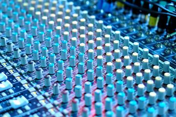 soundboard mixer under blue stage lighting