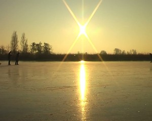 Ice skating  in the Netherlands on a cold winterday at sunset