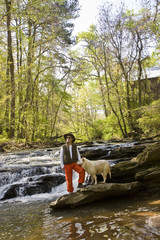 Man Standing on Rock  River  with Dog