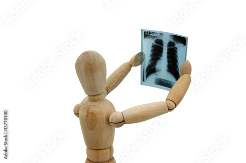 Wooden man looking at x-ray image on white background